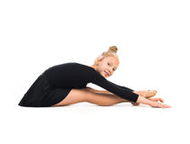 Little gymnast stretching on the floor Stock Photo