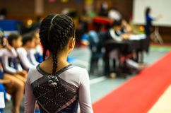 Little gymnast waving to the public in a competition royalty free stock photo