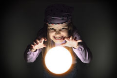 Little Gypsy Fortune Teller. Cute angry little gypsy girl over a glowing crystal ball, predicting the grim future Royalty Free Stock Photo