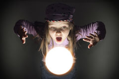 Little Gypsy Fortune Teller. Cute little gypsy girl amazed over a glowing crystal ball, seeing the future Stock Photo