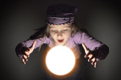 Little Gypsy Fortune Teller. Cute little gypsy girl showing amazement over a glowing crystal ball, predicting the future Stock Photography