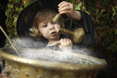 Little halloween witch with cauldron. Outdoors Stock Images