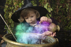 Little halloween witch with cauldron. Outdoors Stock Photo