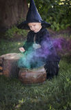 Little halloween witch with couldron outdoors Royalty Free Stock Photos