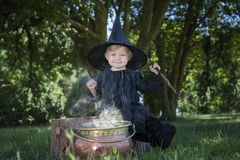 Little halloween witch with couldron outdoors Royalty Free Stock Photography