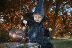 Little halloween witch with couldron outdoors Royalty Free Stock Photo