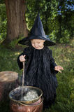 Little halloween witch outdoors with cauldron. Little halloween witch , boiling a potion, outdoors in the woods Royalty Free Stock Images