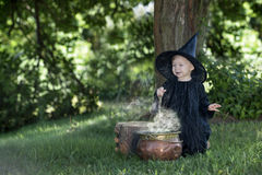 Little halloween witch outdoors with cauldron. Little halloween witch , boiling a potion, outdoors in the woods Stock Image