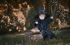 Little halloween witch outdoors in the woods. Little halloween witch , boiling a potion, outdoors in the woods Royalty Free Stock Photography