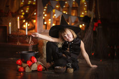 Little Halloween  witch reading conjure above pot   childhood h Royalty Free Stock Photography