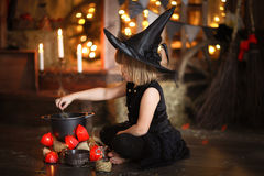 Little Halloween  witch reading conjure above pot   childhood h Stock Images
