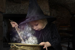 Little halloween witch. With smoking cauldron Stock Image