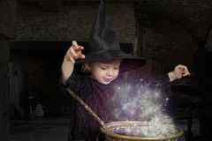 Little halloween witch. With smoking cauldron Stock Images