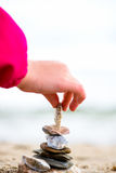 Little Hand placing Stone on the Pyramid on sand. Sea in the bac Stock Photo