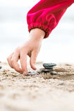Little Hand placing Stone on the Pyramid on sand. Sea in the bac Stock Images