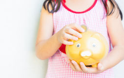 Little hand put coin to piggy bank Royalty Free Stock Photos