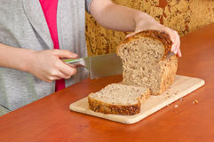Little hands cuts the bread Stock Images