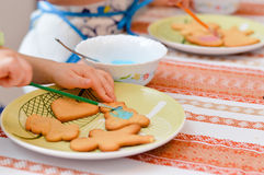 Little hands decorating the gingerbread cookies Royalty Free Stock Photos