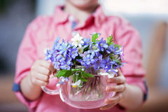 Little hands, holding glass vase with forest spring flower bouqu Stock Image