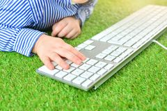 Little hands of kid on computer keyboard. Child and computer game playing concept. stock image