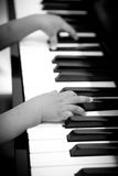Little hands playing on the piano. In black and white Royalty Free Stock Photography