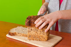 Little hands slicing bread Royalty Free Stock Photos
