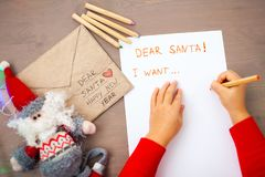 Little hands writting a letter to Santa. Flatlay royalty free stock images
