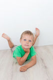 Little handsome boy with blue eyes lying on the floor Royalty Free Stock Photography