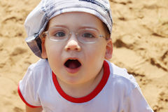 Little handsome boy in cap and glasses surprises Stock Photo