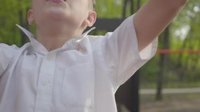 Small handsome boy climbing children`s steps on the playground close-up. Active lifestyle, carefree childhood, adorable. Little handsome boy climbing children`s stock video footage