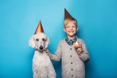 Little handsome boy with dog celebrate birthday. Friendship. Love. Cake with candle. Studio portrait over blue background Stock Image