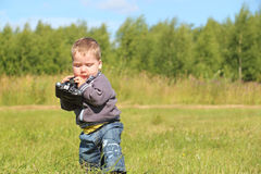 Little handsome boy holds camera and walks at meadow Royalty Free Stock Photo