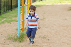 Little handsome boy in shorts. At children playground on sand at summer Royalty Free Stock Photo