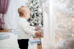 A small child with Christmas decorations in a festive interior. New Year`s and Christmas Royalty Free Stock Photos