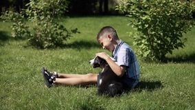 A little boy is playing with a dog in the park.slow motion. Little handsome little boy is playing with a dog in a park. Slow mothion stock footage