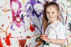 Little happy artist standing in front of painted wal. Little dirty artist standing in front of painted wall, smiling. Creative activity Stock Images