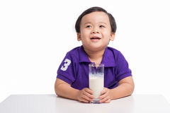 Little happy asian boy with glass of milk isolated on white back stock photography