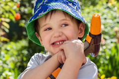 Little happy baby in the garden with a sprinkler for watering the garden, Royalty Free Stock Images