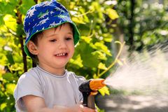 Little happy baby in the garden with a sprinkler for watering the garden, spoiled and showing tongue. Stock Photography