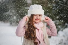 Little happy beautiful girl in winter forest royalty free stock photography