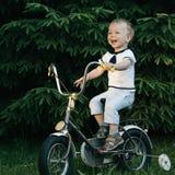 Little happy boy on bike Stock Photos