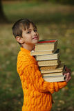 Little happy boy carrying stack of books. Photo of little happy boy carrying stack of books Royalty Free Stock Images