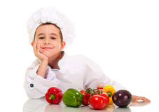 Little happy boy chef in uniform. With vegatables lean on hand isolated on white Royalty Free Stock Photography