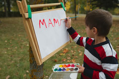 Little happy boy drawing in park Stock Photos