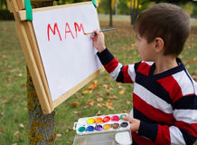 Little happy boy drawing in park Stock Photography