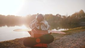Little happy boy in fun old plane pilot costume wearing aviation glasses at amazing sunset forest lake slow motion. Happy male child reflecting and posing at stock footage