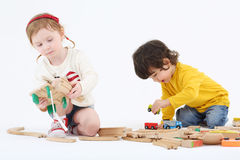 Little happy boy and girl build railway from wooden parts Royalty Free Stock Image