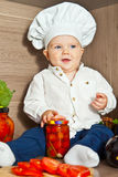 Little happy boy kid play in chef at kitchen and cook food Royalty Free Stock Photo