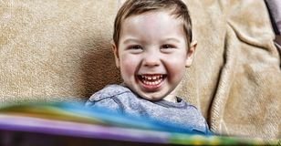 Little happy boy laughing while sitting on the couch. close up. Little happy boy laughing while sitting on the couch at home. close up Royalty Free Stock Photography