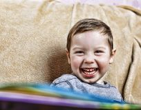 Little happy boy laughing  while sitting on the couch . close up. Little happy boy laughing while sitting on the couch at home Royalty Free Stock Image